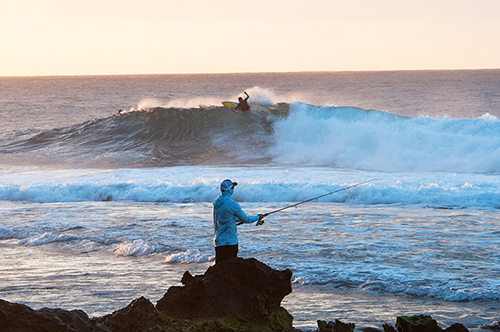 Fisherman and surfer at Rocky Point on Oahu's North Shore